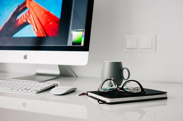 Computer mit Tastatur und Maus. Daneben steht eine Tasse. Außerdem liegt ein Buch daneben worauf eine Brille liegt.